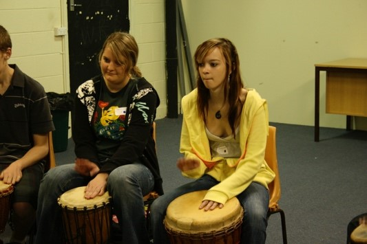 Two young adults during a drumming workshop
